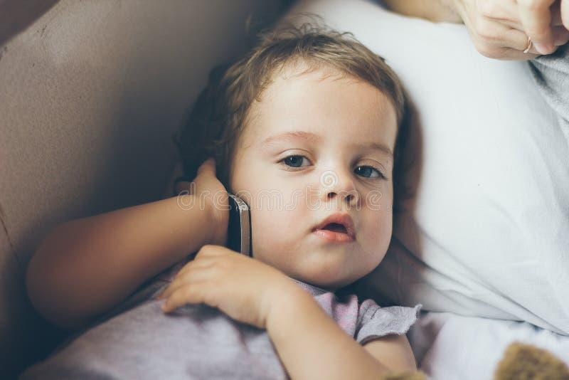 有手机的一个逗人喜爱的相当严肃的女婴 图库摄影