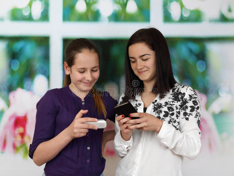 有手机的两个姐妹 库存图片