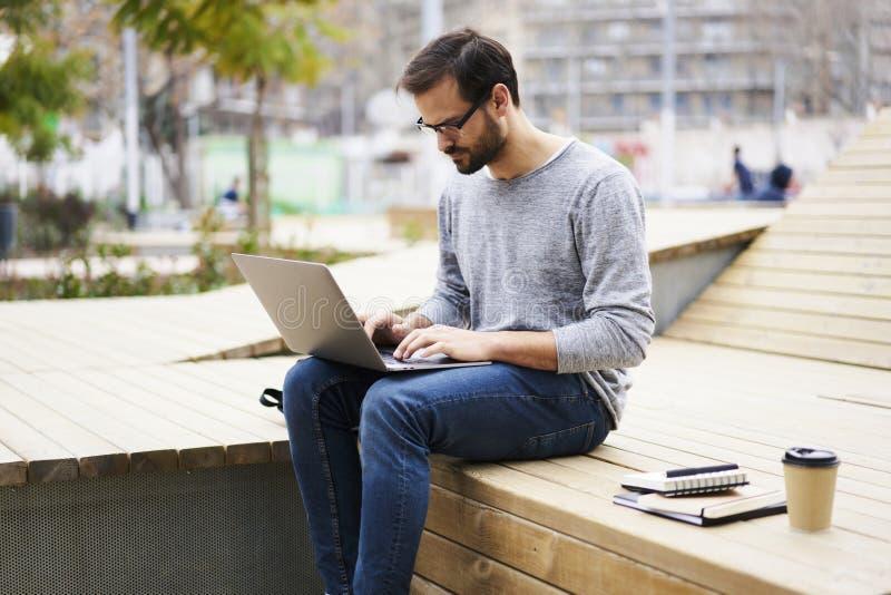 有手机的人使用便携式计算机连接了到无线互联网在校园wifi区域 免版税库存图片