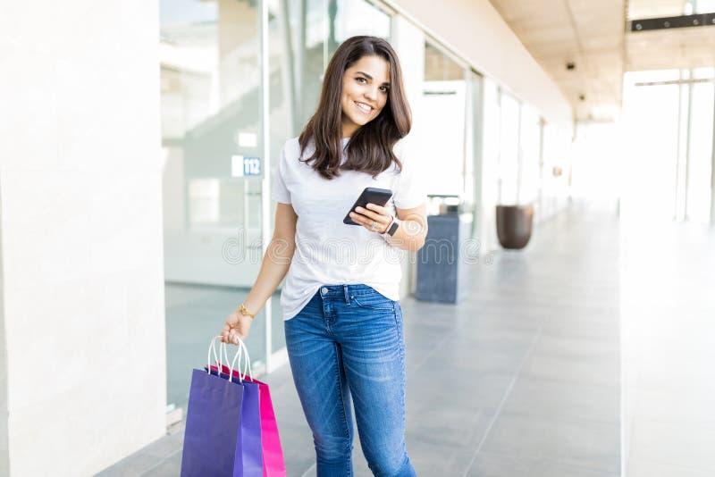有手机的俏丽的妇女和在购物中心的购物袋 免版税库存图片