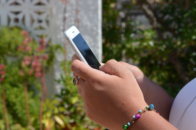 有手机的千福年的妇女在手上,户外 免版税库存图片