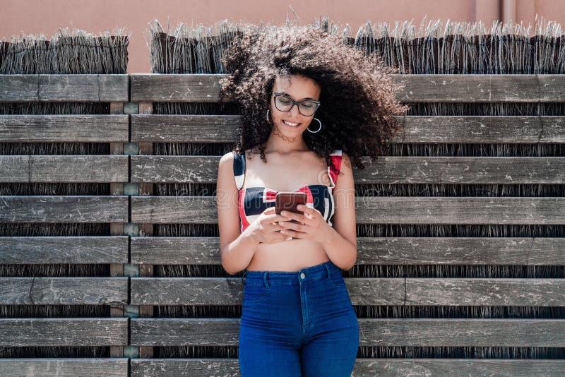 有手机的卷曲女孩在篱笆条篱芭附近 库存照片