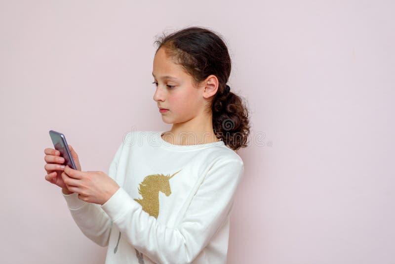 有手机的可爱的行家少年女孩反对桃红色背景 年轻博客作者短信,聊天的电话 库存照片