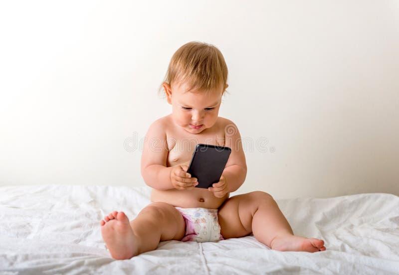 有手机的女婴在她的耳朵附近,告诉某人,拷贝空间,gen z发展 图库摄影