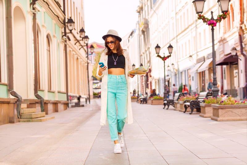 有手机的女孩和城市在街道上映射 免版税库存图片