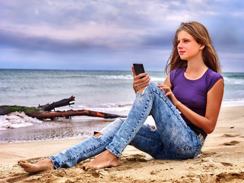 有手机的女孩坐沙子在海附近 免版税图库摄影