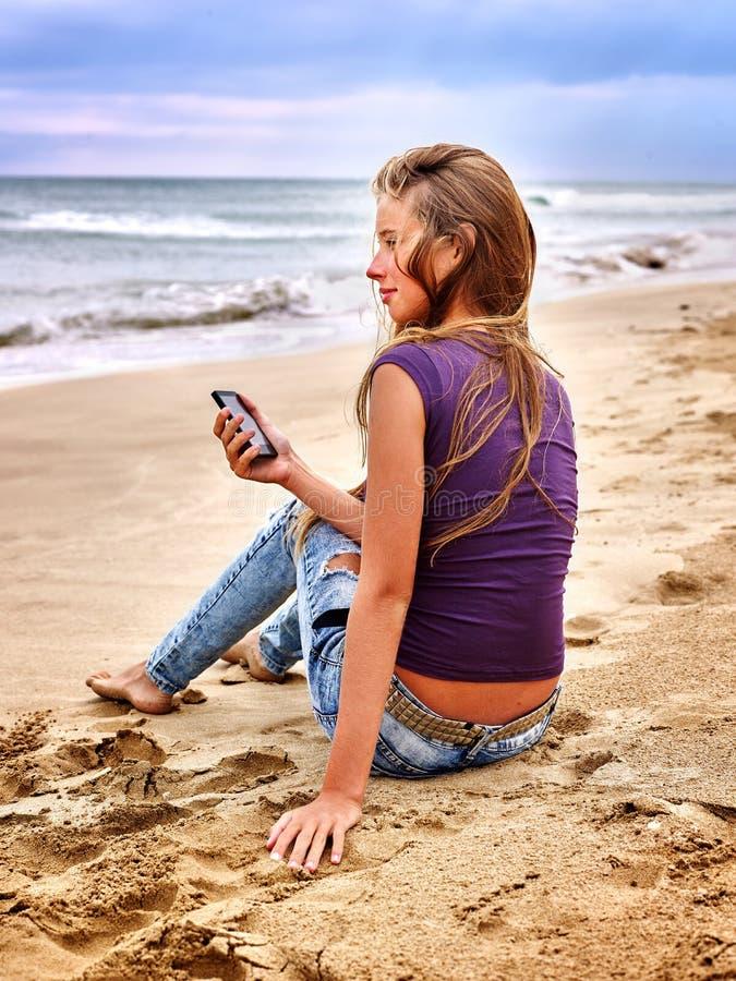有手机的女孩坐沙子在海附近 免版税库存照片