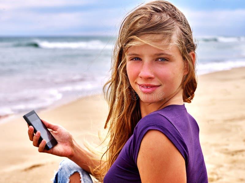 有手机的女孩坐沙子在海附近 库存图片