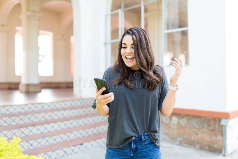 有手机的妇女庆祝她的在大厦之外的胜利 图库摄影