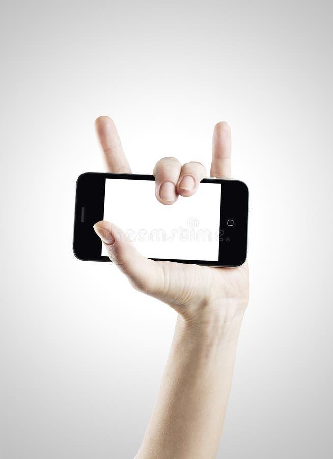 有手机的岩石手 库存图片
