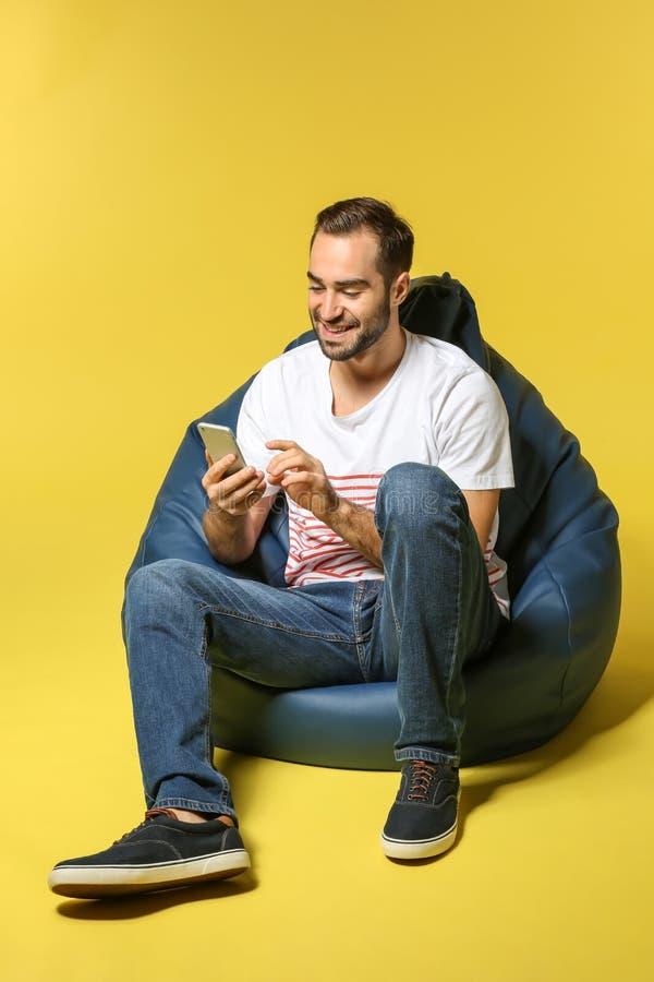 有手机的年轻人坐装豆子小布袋椅子反对颜色背景 库存图片