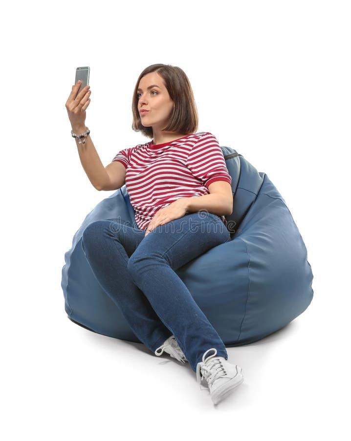 有手机的年轻女人坐装豆子小布袋椅子反对白色背景 库存照片