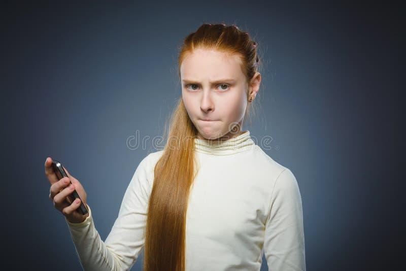 有手机的恼怒的红头发人女孩 查出在灰色 免版税库存照片