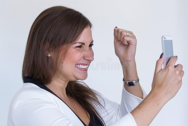 有手机的恼怒的年轻俏丽的女商人 免版税库存照片
