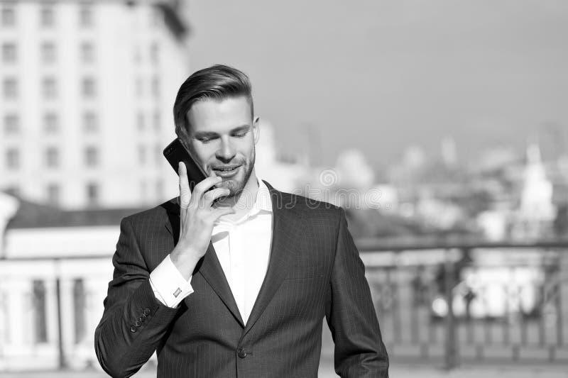 有手机的愉快的人在晴朗的大阳台 商人有微笑的用途智能手机 了不起的商业新闻 事务 免版税库存图片