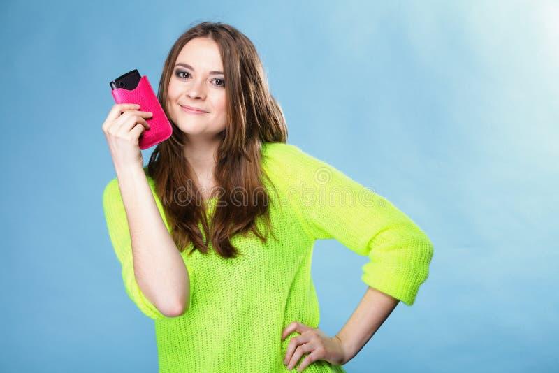 有手机的愉快的女孩在桃红色盖子 免版税库存照片