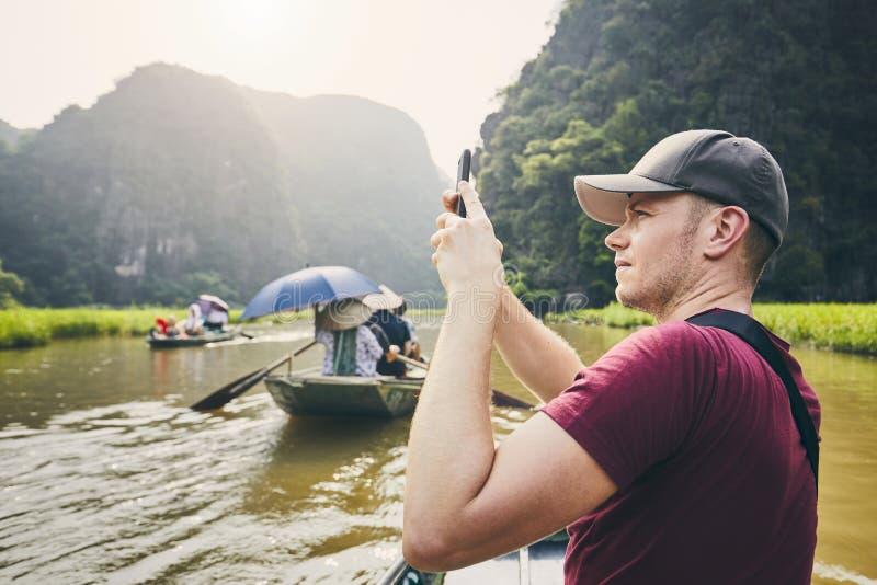 有手机的游人在小船 免版税库存图片