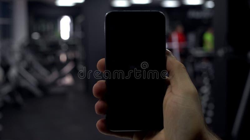 有手机的男性手在健身房,健身应用结果,黑屏幕 库存图片