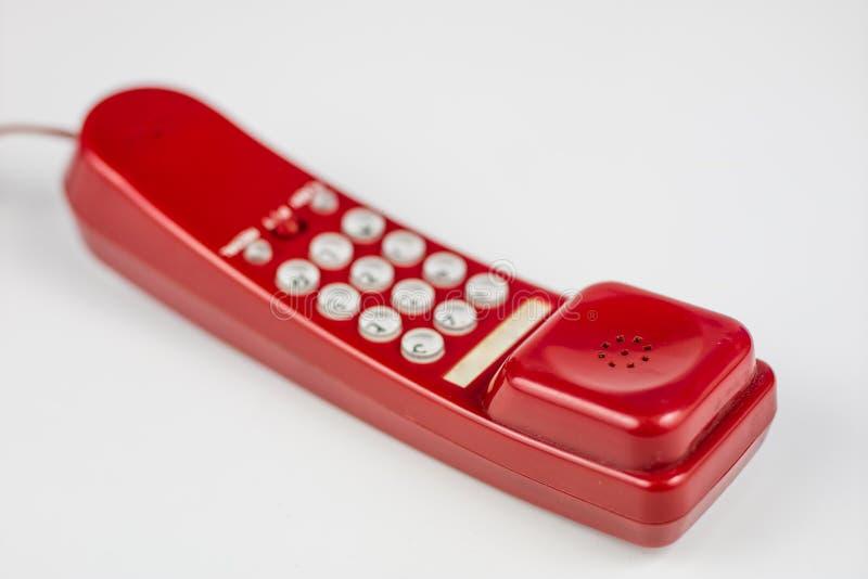 有手机的老红色电话 一个电话机从90 免版税库存照片