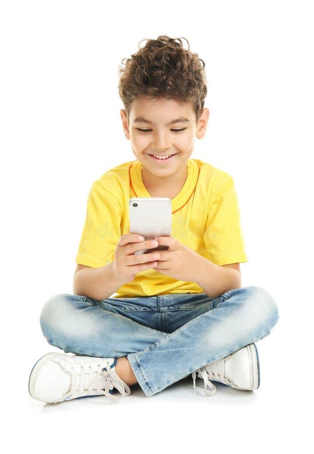 有手机的逗人喜爱的小男孩在白色背景 库存图片