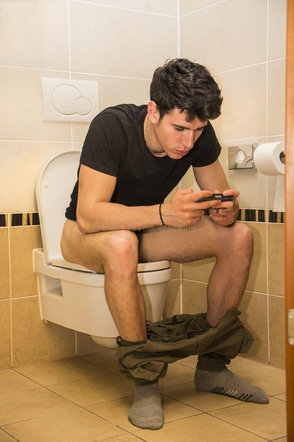 有手机的年轻人坐洗手间 库存图片