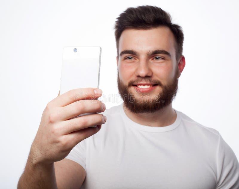 有手机的年轻有胡子的人 库存图片