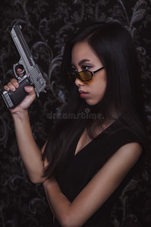 有手枪的亚裔妇女 图库摄影