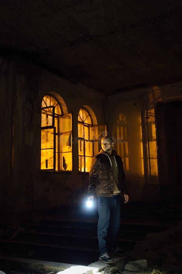 有手电的人在黑暗的蠕动的被放弃的豪宅在晚上 免版税库存照片
