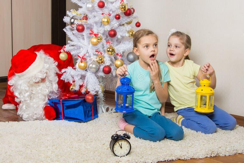 有手电的女孩作梦礼物的在新年夜和圣诞老人被投入出席在圣诞树下 免版税图库摄影