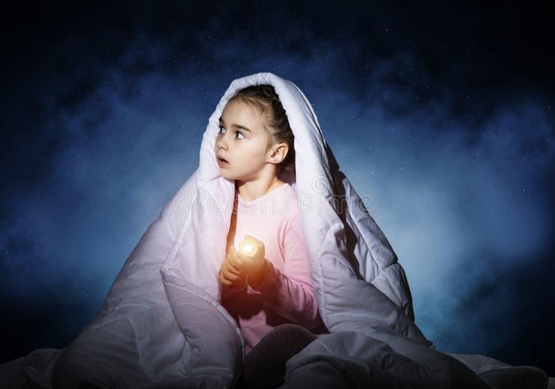 有手电的害怕女孩在毯子下 免版税库存图片