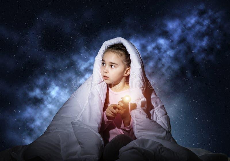 有手电的害怕女孩在毯子下 库存图片