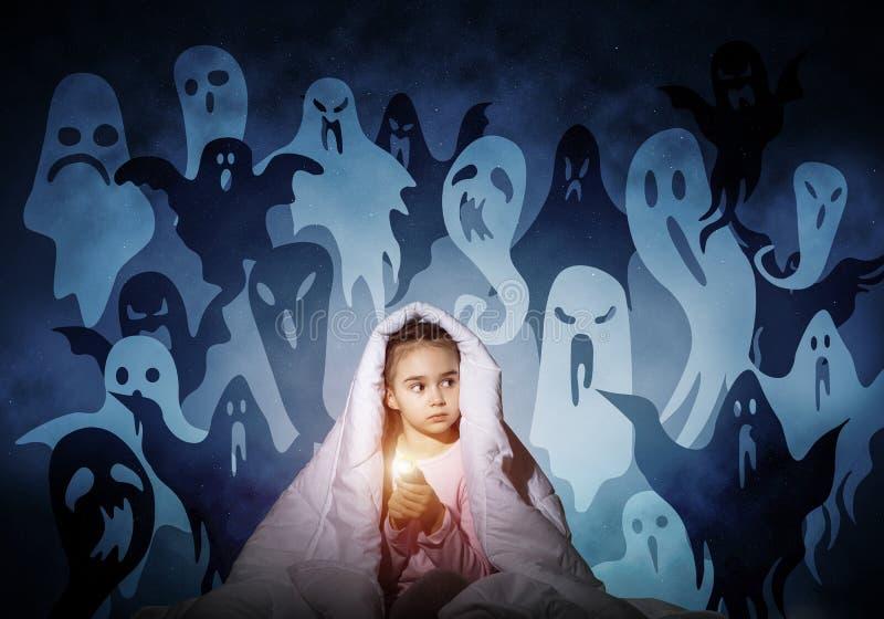 有手电的害怕的女孩在毯子下 库存图片