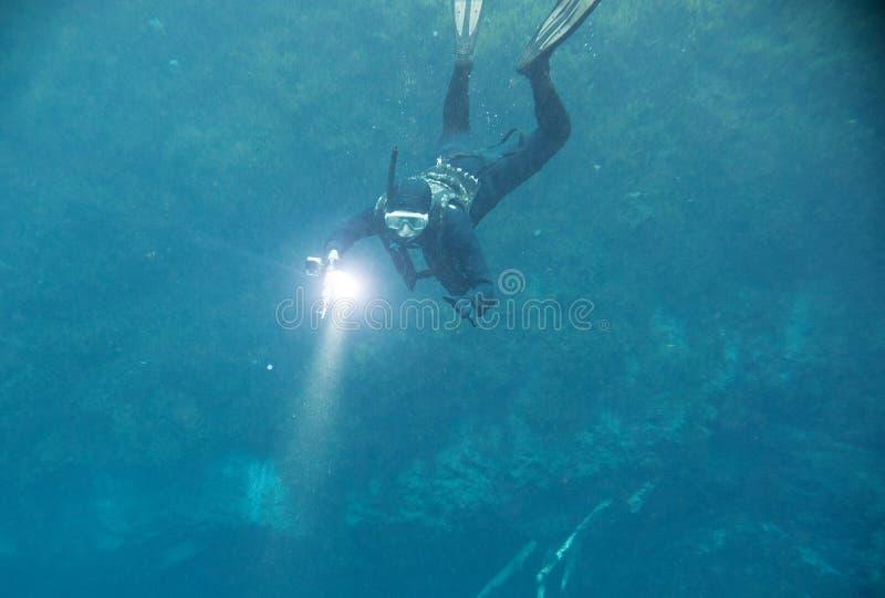 有手电的Spearfishing人在深湖 图库摄影