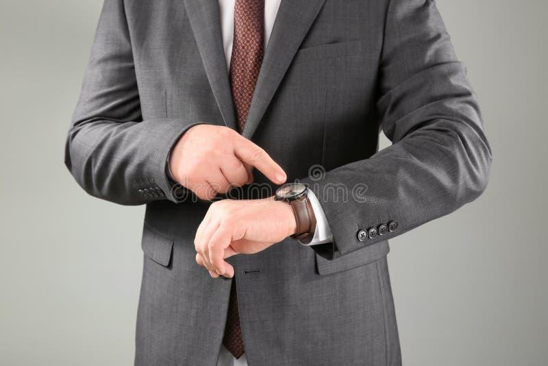 有手表的人反对灰色背景 E 免版税图库摄影