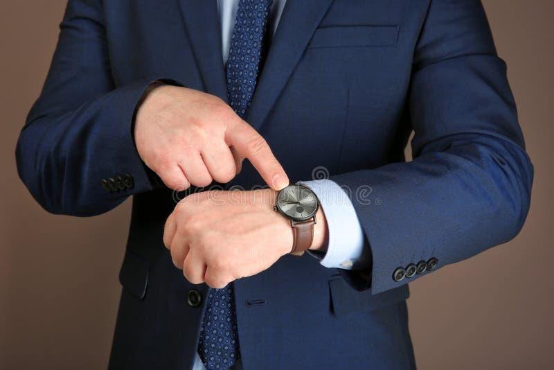 有手表的人反对颜色背景 E 图库摄影