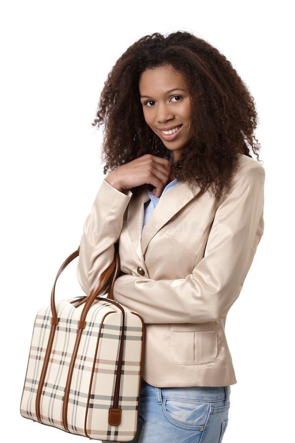 有手袋微笑的可爱的非洲的妇女 免版税库存照片