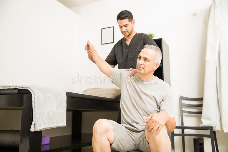 有手锻炼的生理治疗师帮助的病人在诊所 免版税库存图片