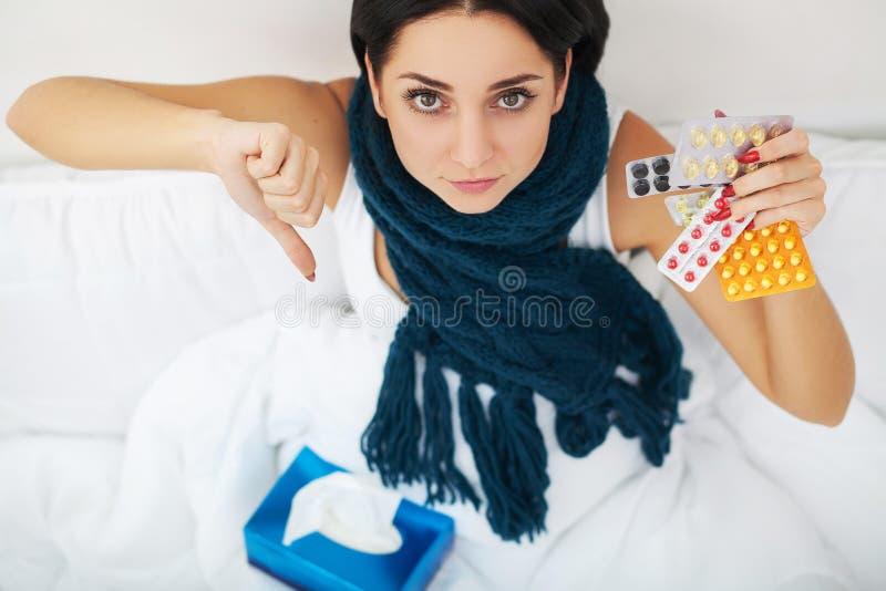 有打喷嚏的鼻子的妇女使用在遭受冷的流感的床上的组织 免版税库存照片
