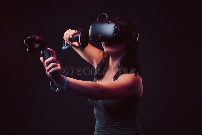 有打电子游戏的虚拟现实耳机和控制杆的美丽的年轻女人 库存照片