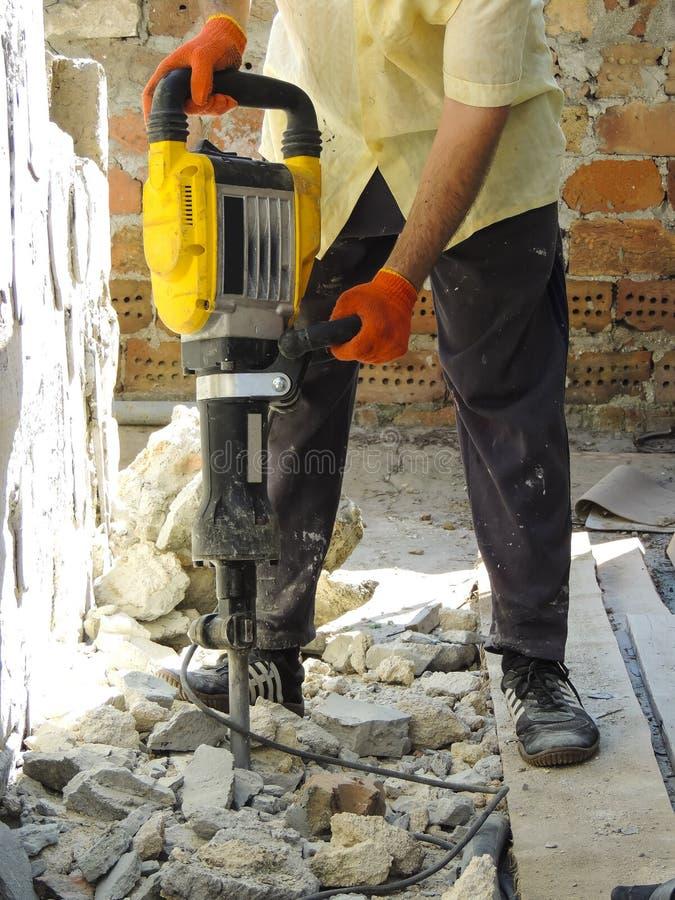 有打破内墙的爆破锤子的工作者 库存照片
