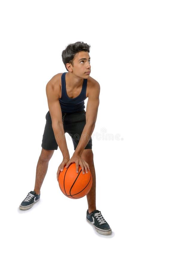 有打篮球的运动服的青少年的运动员 白色backgro 库存图片