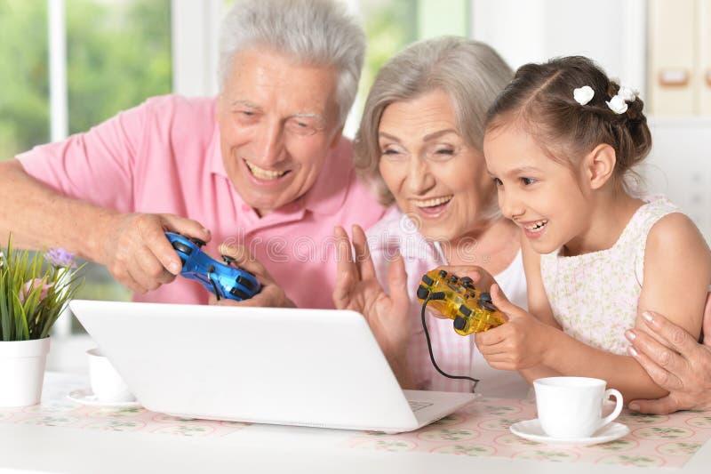 有打计算机游戏的孙女的祖父母 免版税库存照片