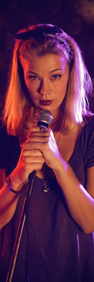有执行在被阐明的阶段的鼓手的确信的女歌手在夜总会 图库摄影