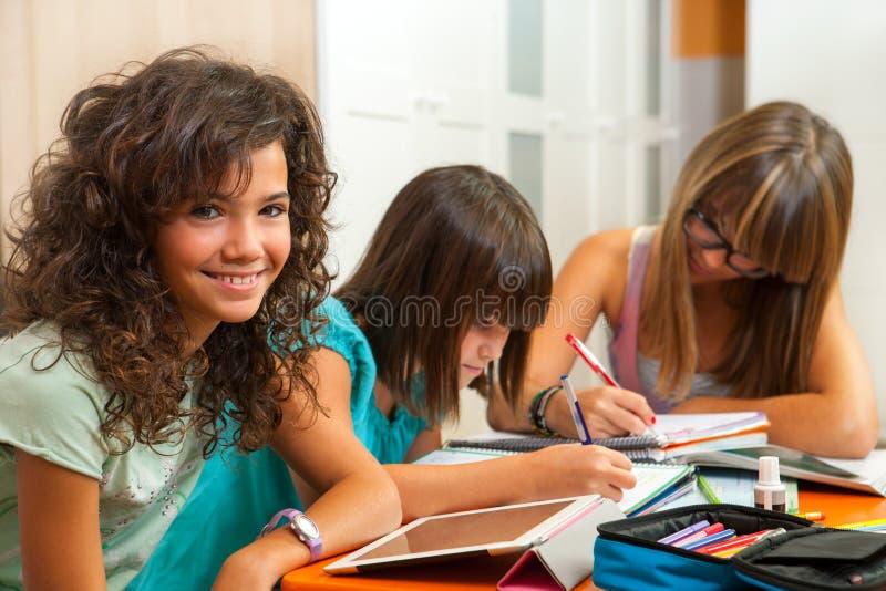 有执行家庭作业的朋友的十几岁的女孩。 库存图片