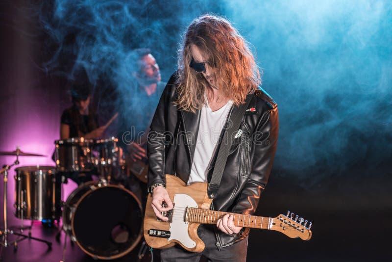 有执行硬岩音乐的摇滚乐队的电吉他球员 免版税库存照片