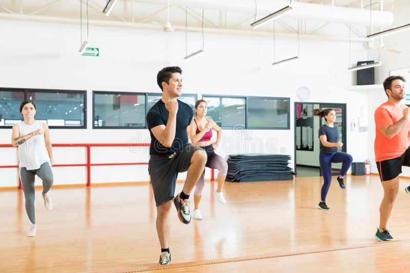 有执行高膝盖的朋友的人跑在增氧健身班 免版税库存图片