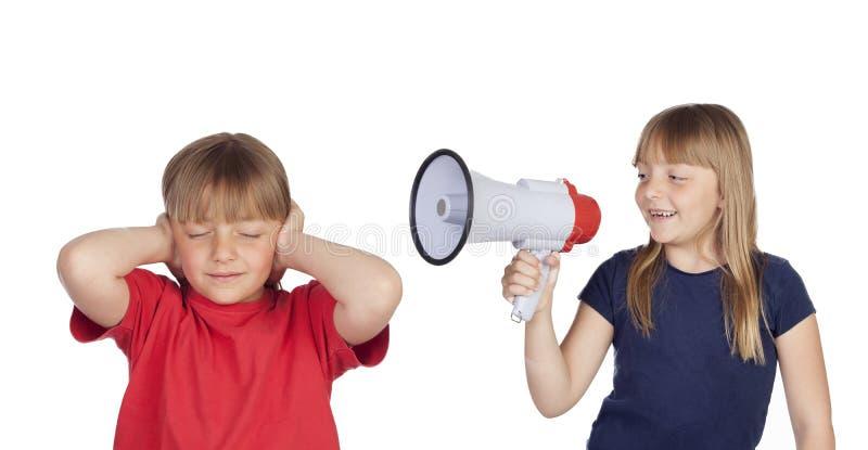 有扩音机的小女孩呼喊对她的双姐妹的 库存图片