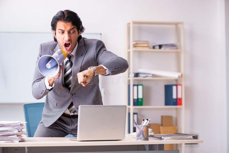 有扩音机的年轻雇员上司在办公室 免版税图库摄影