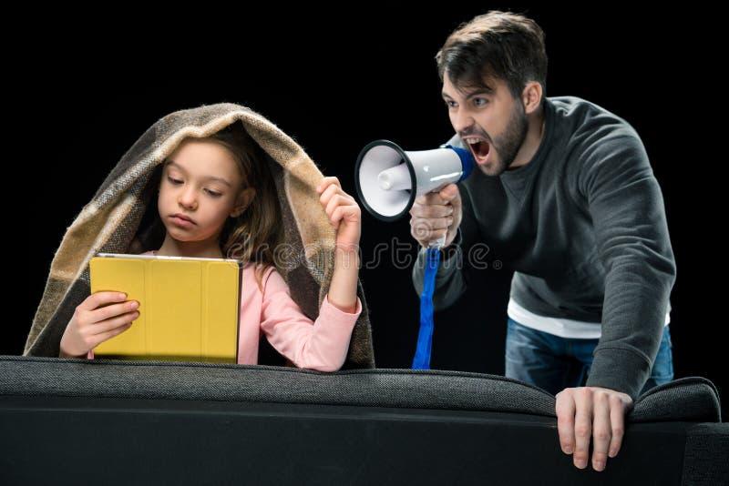 有扩音机的恼怒的父亲尖叫对使用数字式片剂的翻倒女儿 图库摄影