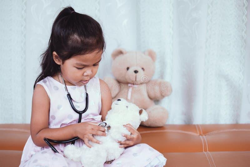 有扮演医生的听诊器的逗人喜爱的亚裔小孩女孩 免版税图库摄影
